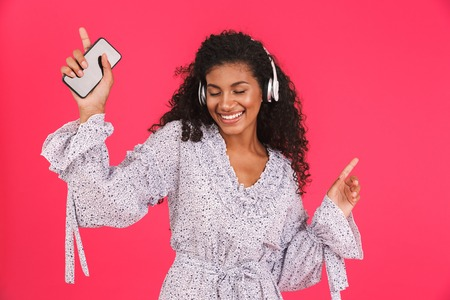 Portrait of a smiling young african woman in summer dress standing isolated over pink background, listening to music with headphones, holding mobile phone Imagens - 109436917