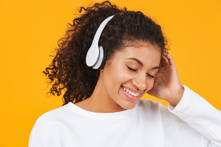 Portrait of a happy young african woman standing isolated over yellow background, listening to music with headphones Imagens - 109436938