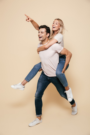 Full length portrait of a cheerful young couple standing together over beige background, piggyback ride, pointing finger away