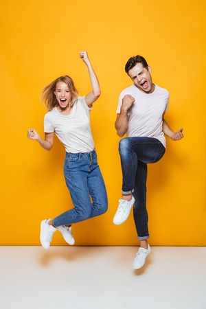 Full length portrait of happy young couple jumping isolated over yellow background