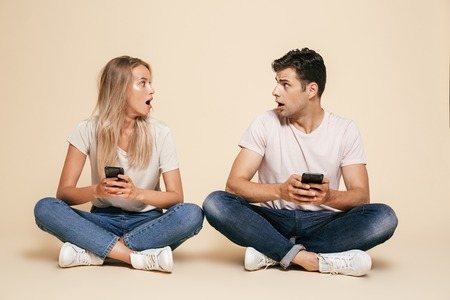 Portrait of a shocked young couple sitting together over beige background, holding mobile phones Stock Photo