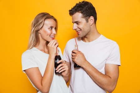 Smiling young couple standing isolated over background, drinking fizzy drink from a glass bottle, looking at each other
