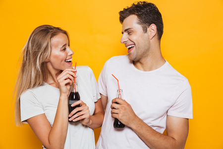 Happy young couple standing isolated over yellow background, drinking fizzy drink from a glass bottle, looking at each other Foto de archivo - 108972233