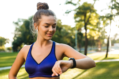 Photo of beautiful young sports woman in park outdoors listening music with earphones looking at watch.