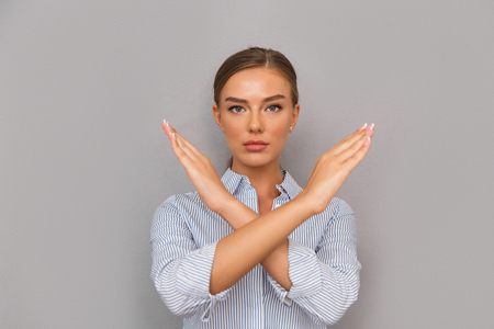 Serious young businesswoman standing over gray background, showing crossed arms gesture