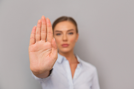 Confident young businesswoman standing over gray background, showing stop gesture Stock Photo