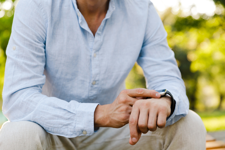 Cropped image of a young casual man adjusting his smart watch while sitting at the city park Stockfoto