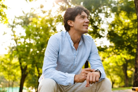 Smiling young casual man adjusting his smart watch while sitting at the city park