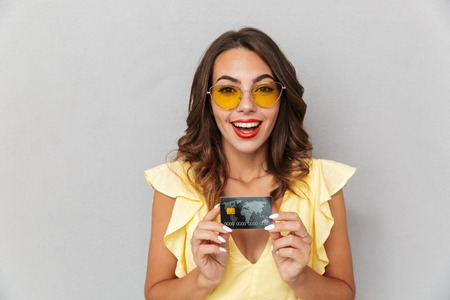 Portrait of a satisfied young girl in dress standing over gray background, showing plastic credit card Stock Photo