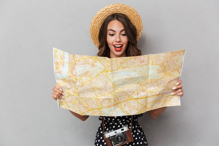 Image of excited young cute woman wearing hat holding map over grey wall.