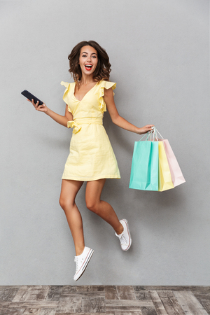 Full length portrait of a happy young girl in dress jumping over gray background, holding mobile phone, carrying shopping bags Stock Photo