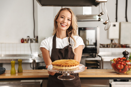 Smiling young woman chef cook in apron standing at the kitchen, showing tasty pie Stockfoto