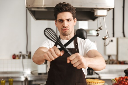 Furious young man chef cook in apron standing at the kitchen, holding ladle and whisk
