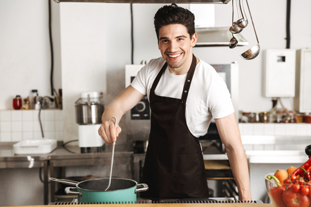 Happy young man chef cook in apron standing at the kitchen, stirring soup Фото со стока
