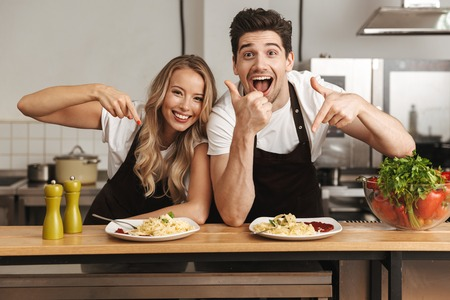 Image of happy excited young friends loving couple chefs on the kitchen eat tasty pasta make thumbs up pointing. Stockfoto
