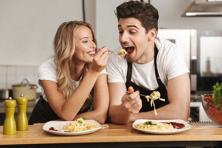 Wizerunek szczęśliwych podekscytowanych młodych przyjaciół kochających kucharzy para w kuchni jedzą smaczny makaron.