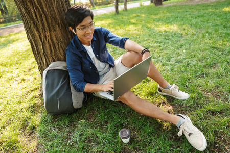 Happy asian male student in eyeglasses using laptop computer while sitting near the tree in park