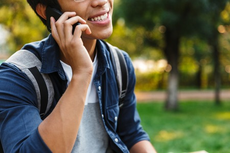 Cropped image of Happy asian male student talking by smartphone while sitting in park Banco de Imagens