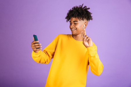 Portrait of young african american man smiling and taking selfie on smartphone, wearing bluetooth earpod isolated over violet background