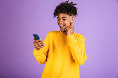 Portrait of joyful african american man smiling and holding smartphone, wearing bluetooth earpod isolated over violet background Stock Photo