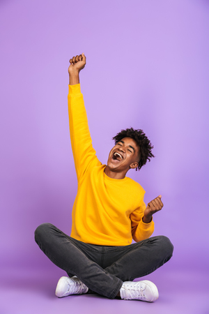 Portrait of young african american boy smiling and rejoicing while sitting on floor with legs crossed isolated over violet background