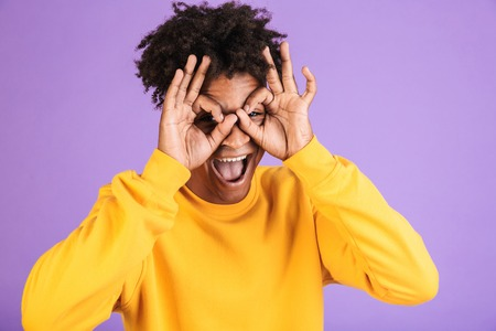 Portrait of a happy young afro american man dressed in sweatshirt showing ok isolated