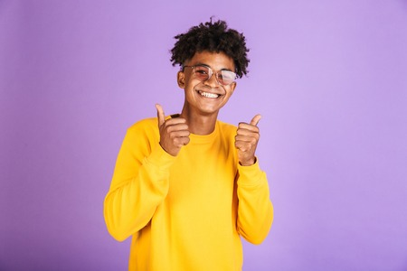 Portrait of a happy young afro american man in sweatshirt isolated, showing thumbs up