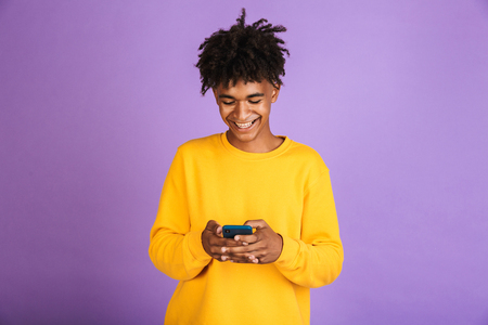 Portrait of stylish american guy smiling and holding smartphone isolated over violet background