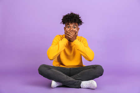 Portrait of shocked african american boy sitting on floor with legs crossed and covering mouth with hands isolated over violet background