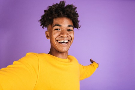 Portrait of a cheerful young afro american man dressed in sweatshirt taking a selfie isolated
