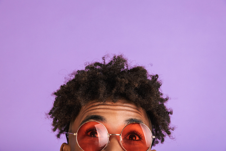Half face portrait of a young afro american man in sunglasses isolated, looking up