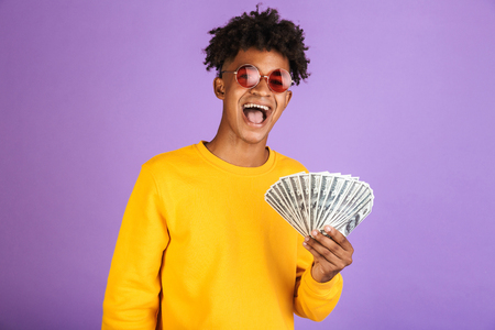 Portrait of fashion african american man wearing sunglasses smiling while holding cash money dollars isolated over violet background