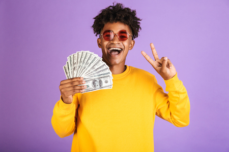 Portrait of stylish african american man wearing sunglasses smiling while holding dollars money banknotes isolated over violet background