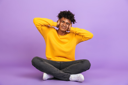 Portrait of unhappy african american boy sitting on floor with legs crossed and covering ears with hands isolated over violet background
