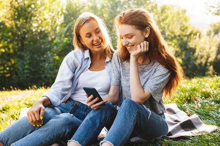 Two happy youg girls having fun at the park, holding mobile phone while sitting on a grass