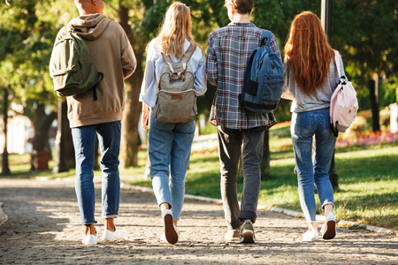 Back view group of students with backpacks walking at the campus outdoors Stock Photo