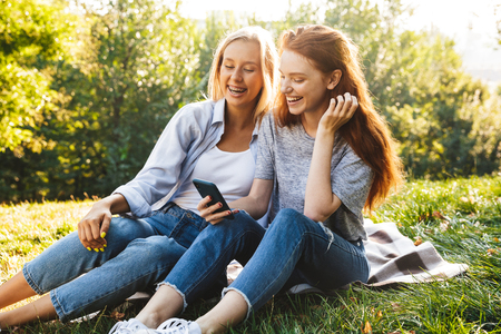 Two cheerful youg girls having fun at the park, holding mobile phone while sitting on a grass Stock Photo