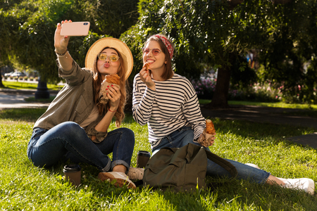 Two happy young girls friends having fun at the park, taking a selfie, having a picnic