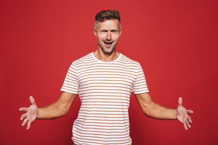 Caucasian man in striped t-shirt gesturing and demonstrating size with copyspace isolated over red background
