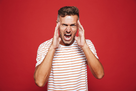 Furious adult man in striped t-shirt screaming and touching face isolated over red background Фото со стока
