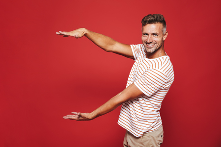 Joyous guy in striped t-shirt gesturing and demonstrating size with copyspace isolated over red background
