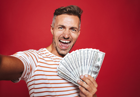 Photo of delighted man in striped t-shirt smiling and taking selfie while holding fan of money banknotes isolated over red background