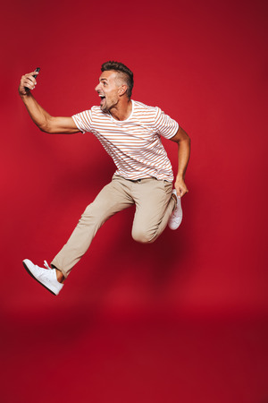 Full length photo of optimistic man in striped t-shirt jumping and taking selfie on smartphone isolated over red background