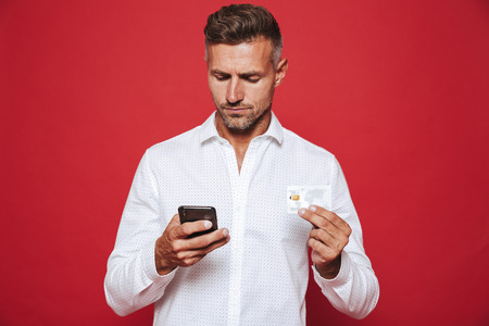 Photo of adult man in white shirt holding credit card and smartphone isolated over red background Stock Photo