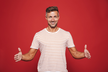 Successful man 30s in striped t-shirt gesturing and demonstrating size with copyspace isolated over red background Stock Photo