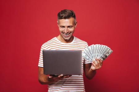 Photo of young man 30s in striped t-shirt smiling while holding fan of money banknotes and laptop isolated over red background