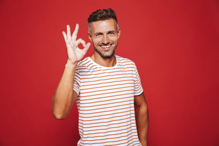 Brunette young man in striped t-shirt smiling and showing ok sign isolated over red background 写真素材