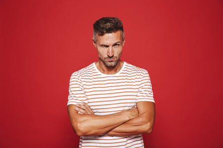 Irritated man 30s in striped t-shirt standing with arms crossed and angry look isolated over red background