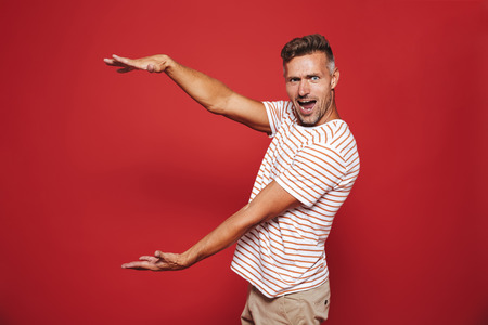 Excited man in striped t-shirt gesturing and demonstrating size with copyspace isolated over red background
