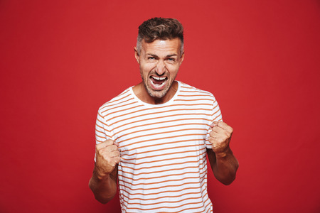 Emotional furious man in striped t-shirt screaming and showing fists isolated over red background